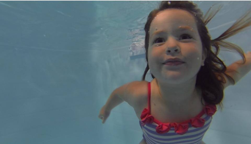 Child swimming underwater during lesson